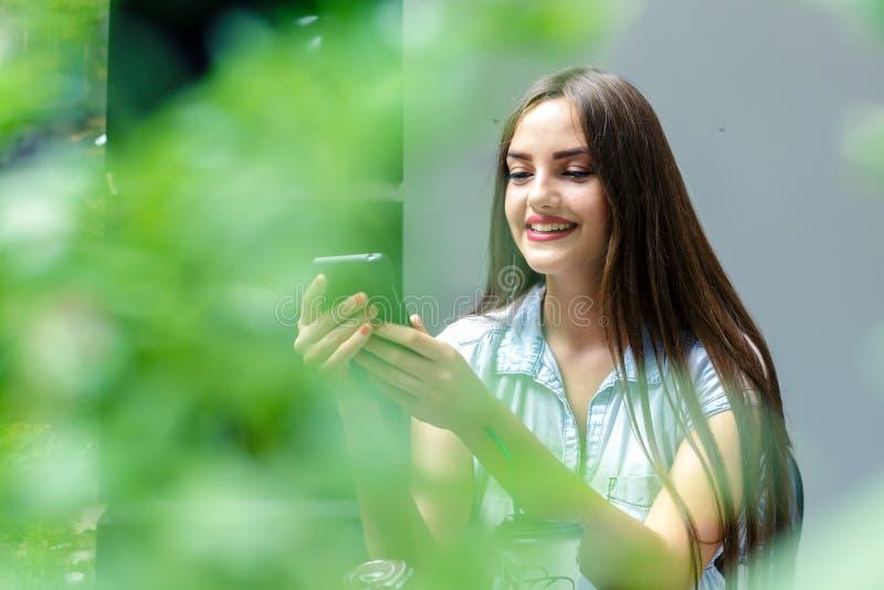 使用智能手机的美丽的微笑的女孩在室外咖啡馆 库存照片