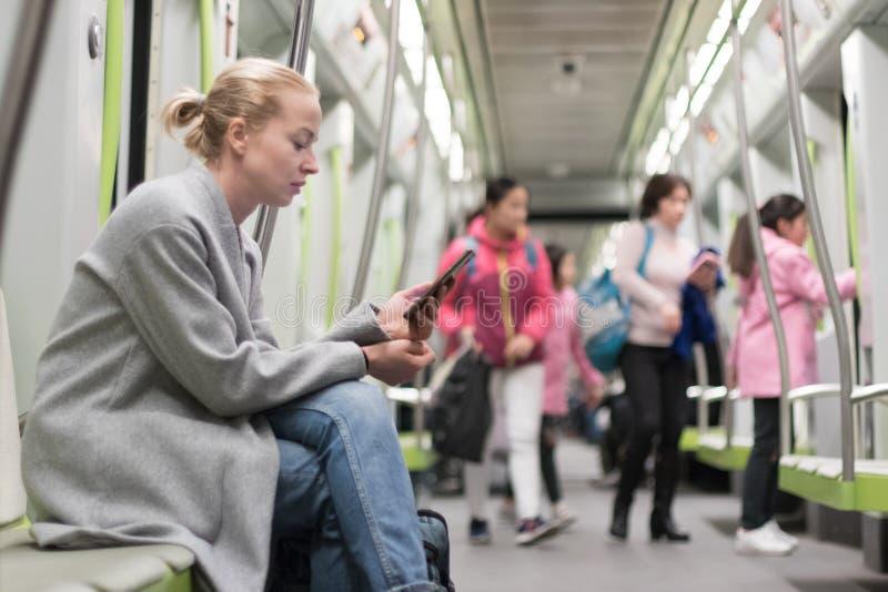 使用智能手机的美丽的白肤金发的妇女,当旅行由地铁公共交通工具时 免版税图库摄影
