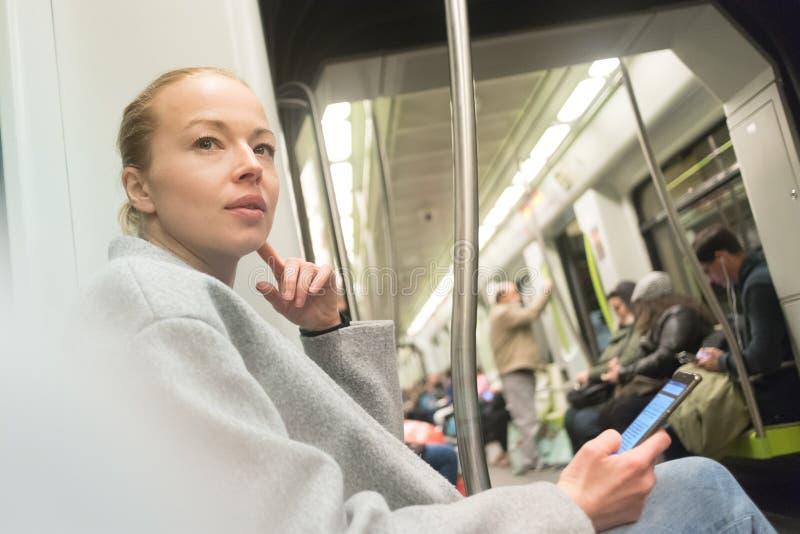 使用智能手机的美丽的白肤金发的妇女,当旅行由地铁公共交通工具时 图库摄影