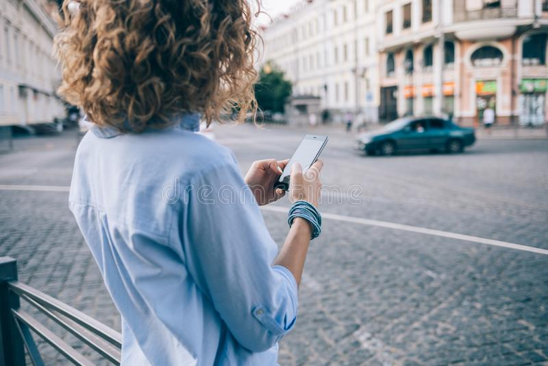 使用智能手机的背面图无法认出的卷曲年轻女人 免版税库存图片