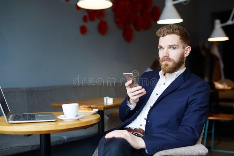 使用智能手机的英俊的人在咖啡馆 免版税库存照片