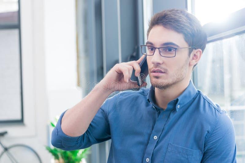 使用智能手机的英俊的商人 库存照片