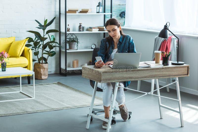 使用智能手机的被聚焦的女孩,当学习与膝上型计算机时 免版税库存图片
