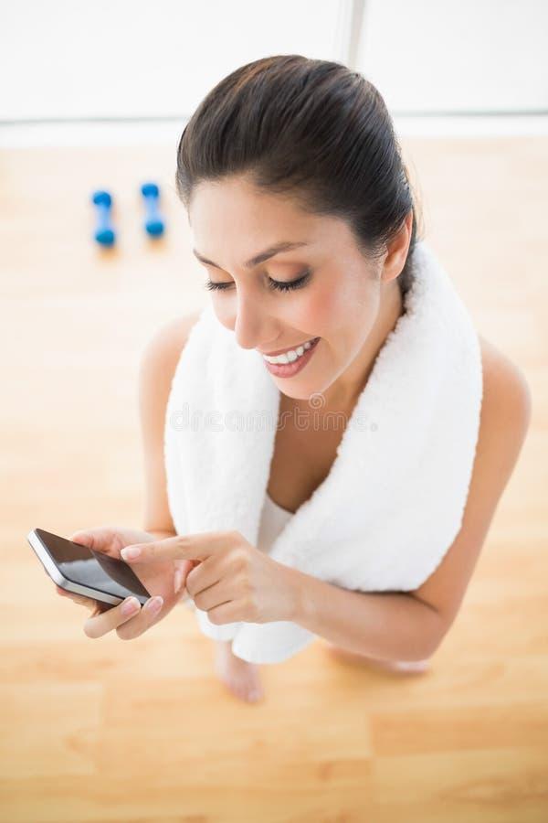 使用智能手机的适合的妇女从锻炼的休假 库存照片