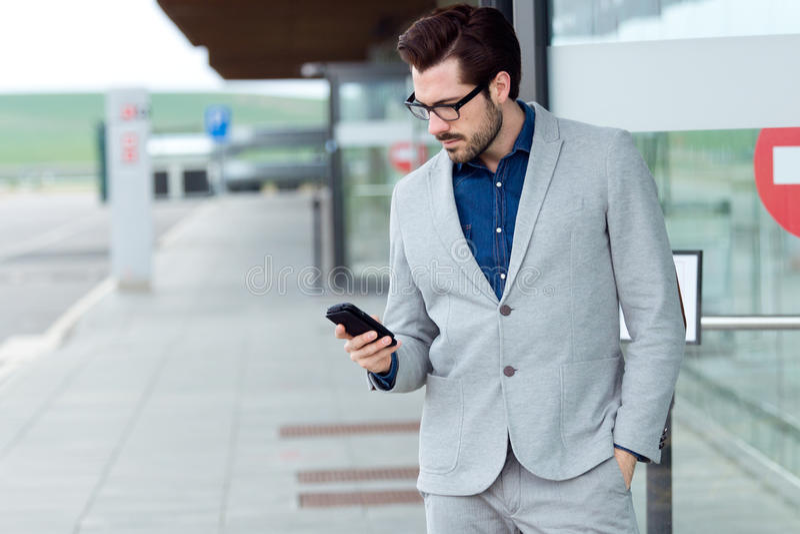 使用智能手机的都市商人 免版税库存图片