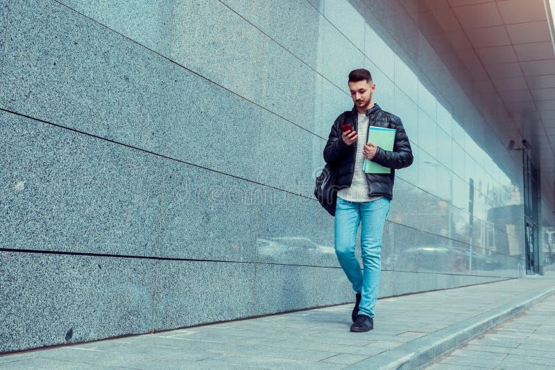 使用智能手机的阿拉伯学生在市中心 去大学的年轻人 免版税库存图片