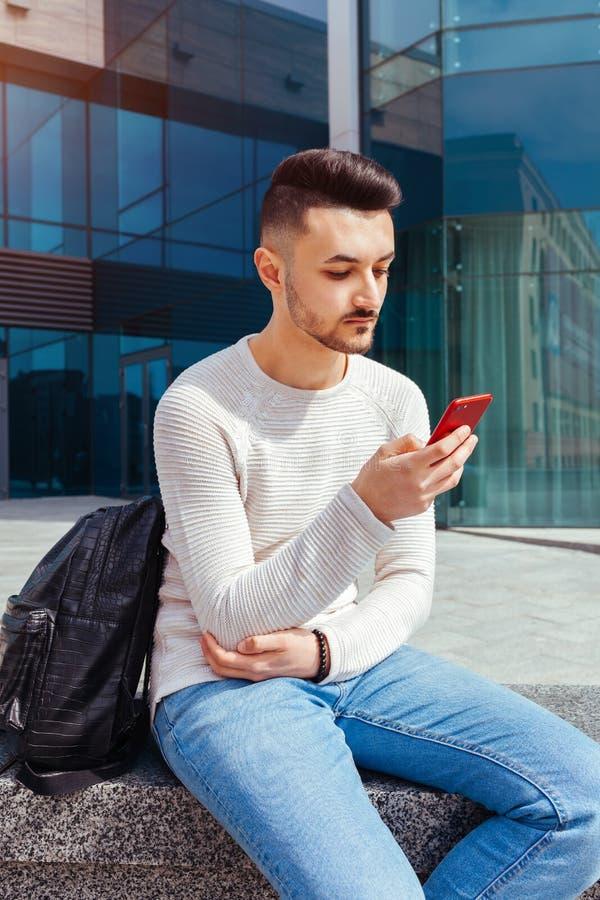 使用智能手机的阿拉伯学生外面 严肃的人看在现代大厦前面的电话在类以后 库存图片