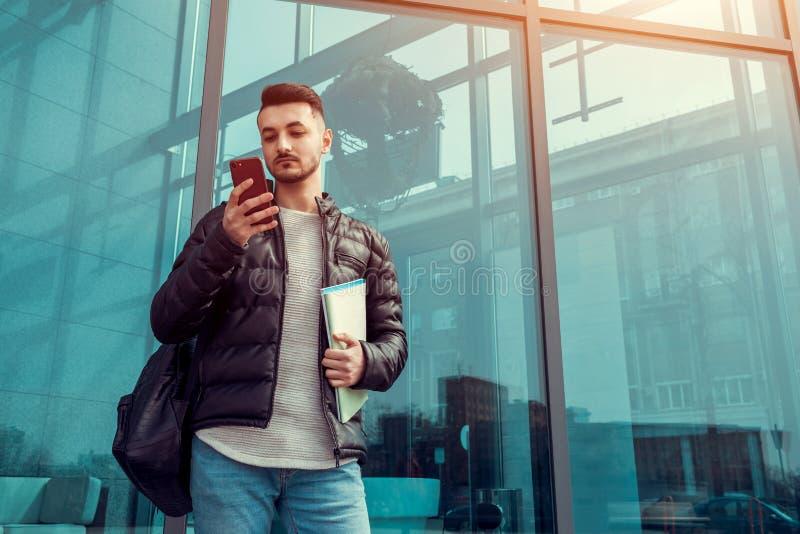 使用智能手机的阿拉伯学生外面 严肃的人看在现代大厦前面的电话在类以后 免版税库存图片