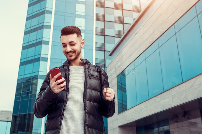 使用智能手机的阿拉伯学生外面 人成功的年轻人 激动的人看在现代大厦前面的电话 免版税库存图片