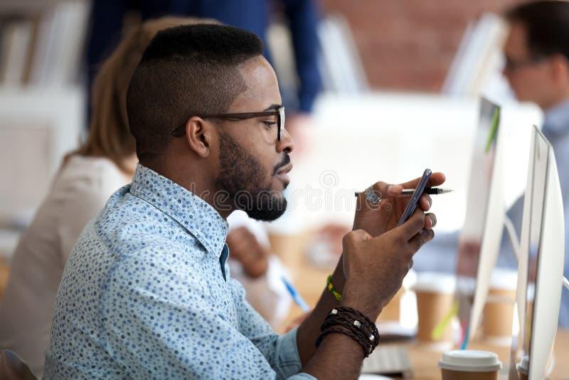 使用智能手机的非裔美国人的男性工作者在工作 免版税库存照片