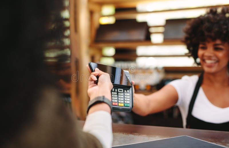 使用智能手机的顾客付帐 库存照片