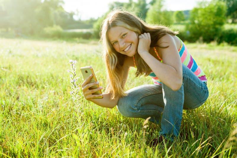 使用智能手机的年轻十几岁的女孩,拍摄花  免版税库存图片