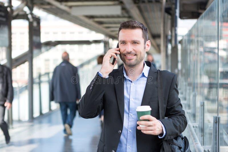 使用智能手机的年轻可爱的商人,当喝co时 免版税库存照片