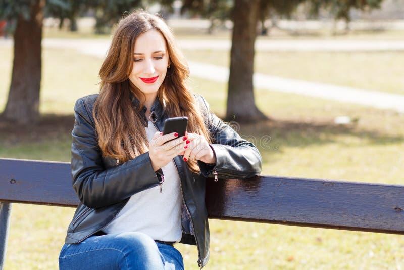 使用智能手机的年轻微笑的妇女在公园 库存照片