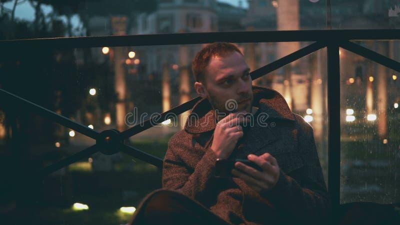 使用智能手机的年轻英俊的人,平衡背景的城市 人浏览有触摸屏幕技术的互联网 免版税库存照片