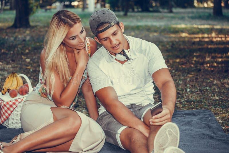 使用智能手机的Happx年轻夫妇在野餐期间在公园 免版税库存照片