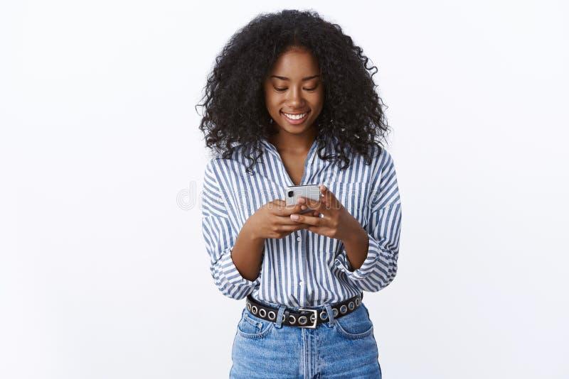 使用智能手机笑的愉快微笑的迷人的可爱的卷发的深色皮肤的妇女宜人的交谈 免版税库存图片