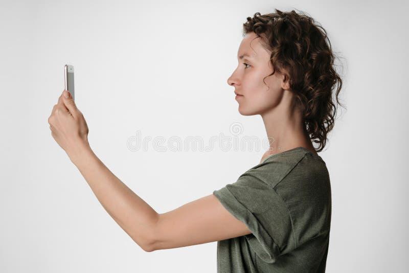 使用智能手机面貌识别的年轻卷发妇女隔绝在白色 免版税库存图片