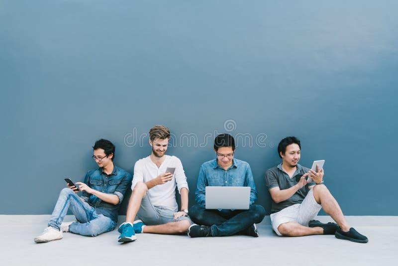 使用智能手机,便携式计算机,与拷贝空间一起的数字式片剂的不同种族的小组四个人在蓝色墙壁上 库存照片