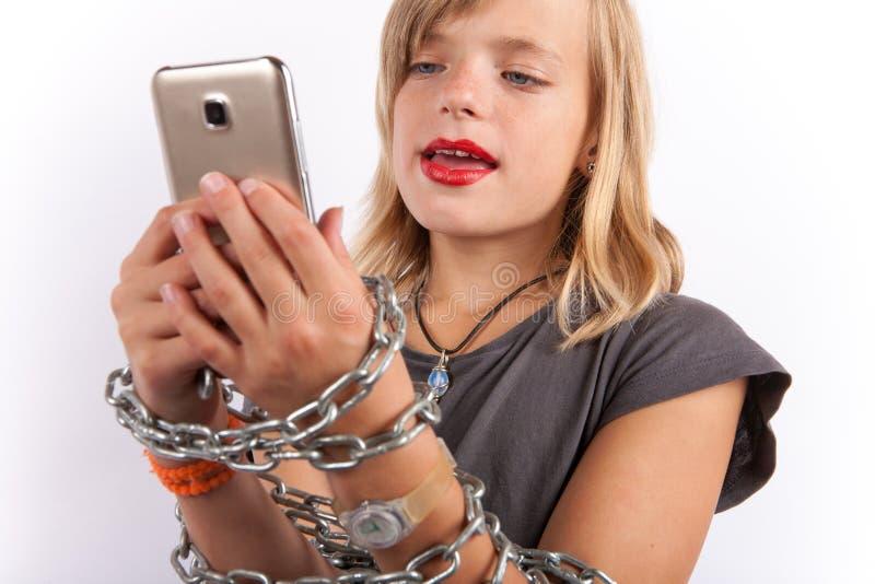 使用智能手机,女孩桎梏了与链子 免版税库存图片