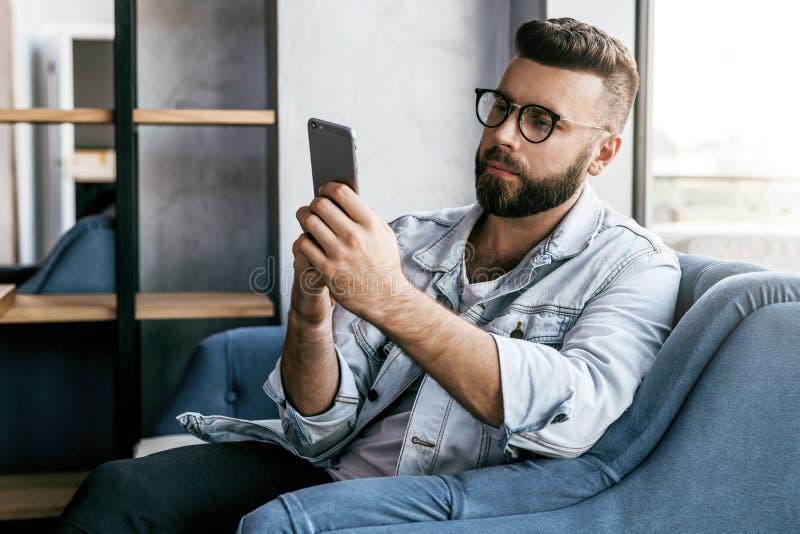 使用智能手机,年轻微笑的有胡子的商人在咖啡馆坐, 自由职业者工作在咖啡馆 在线教育 免版税库存图片