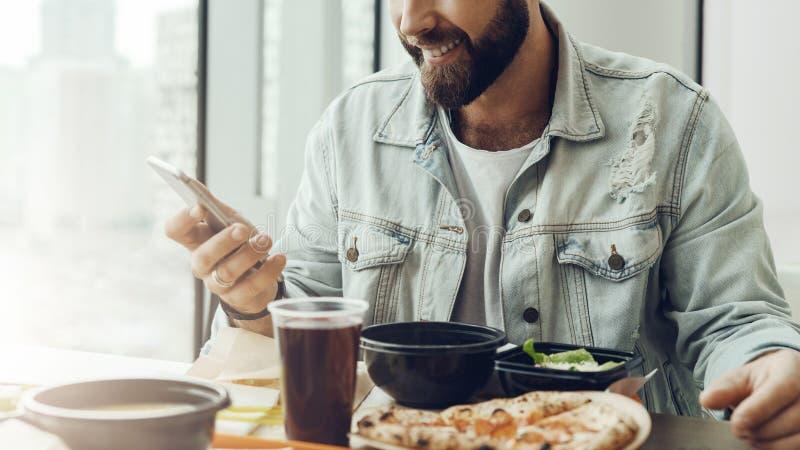 使用智能手机,行家人在咖啡馆坐在桌上,吃午餐, 使用流动应用,人支付命令在餐馆 库存照片