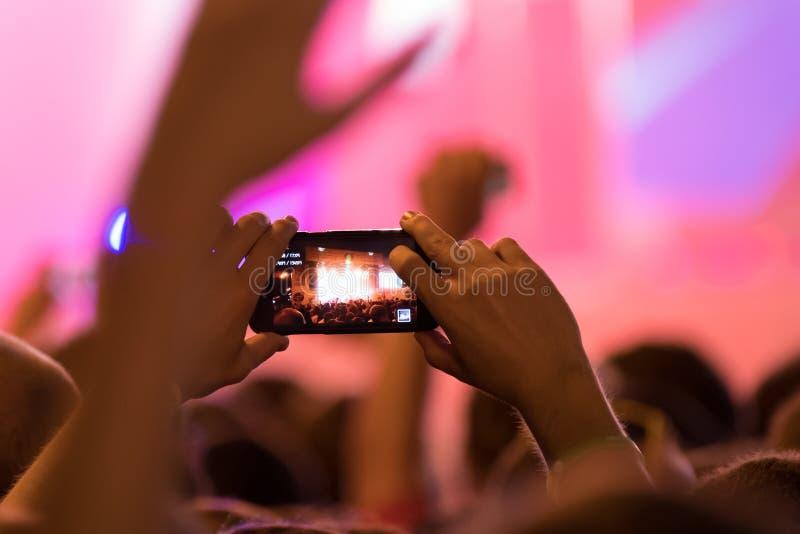 使用智能手机,访客纪录居住音乐会 免版税库存照片