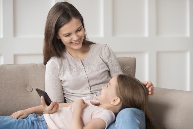 使用智能手机,说谎在母亲膝部的女儿一起花费时间 库存图片