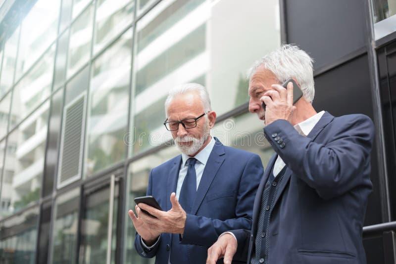 使用智能手机,谈话和传讯的两个愉快的资深商人 免版税图库摄影
