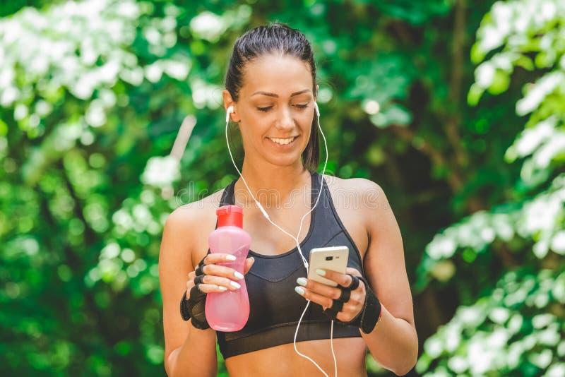 使用智能手机app的女运动员和走在公园 库存图片