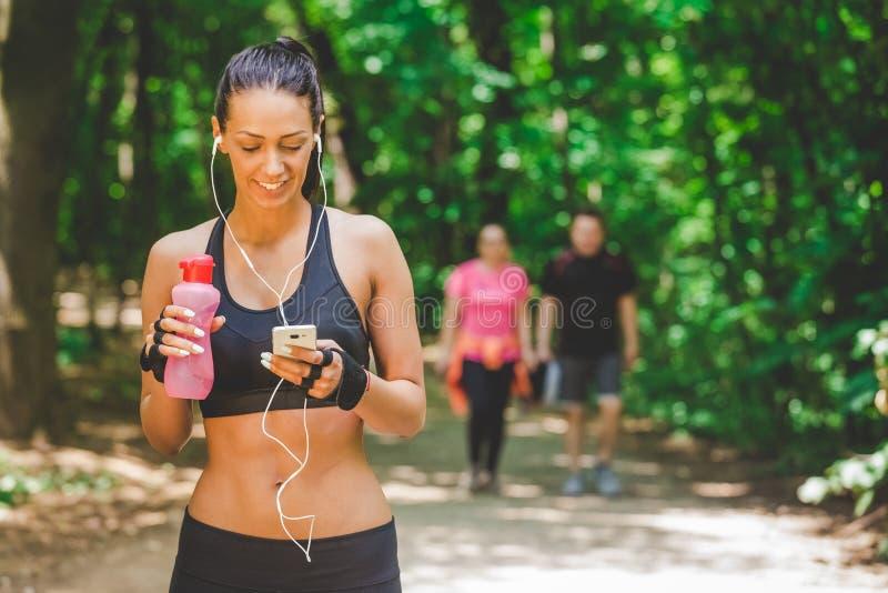 使用智能手机app的女运动员和走在连续轨道在公园 库存照片