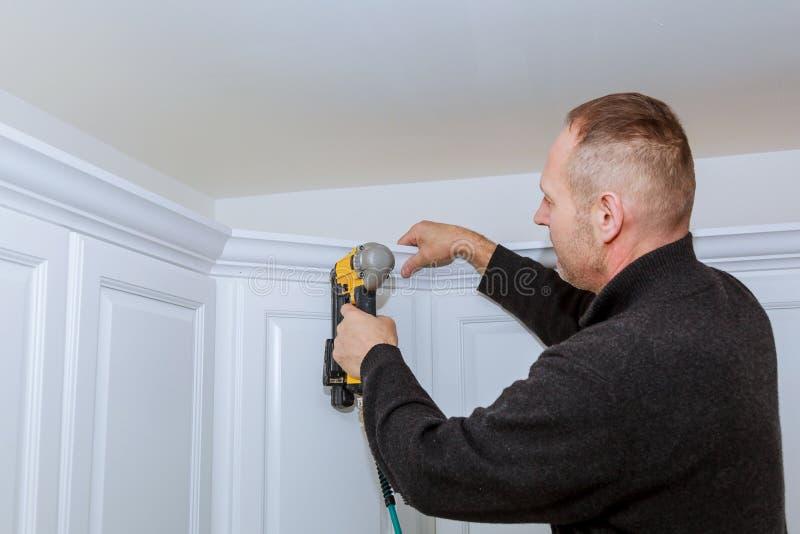使用曲头钉钉子气枪的建筑工人加冠铸造在构筑修剪的白色厨房壁柜, 免版税库存照片