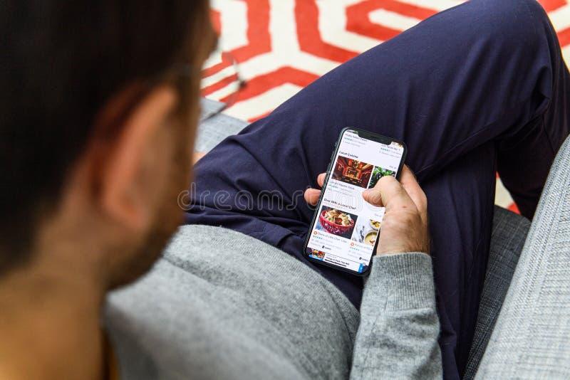 使用最新的iPhone XS的人在箱中取出Tripadvisors以后app 图库摄影