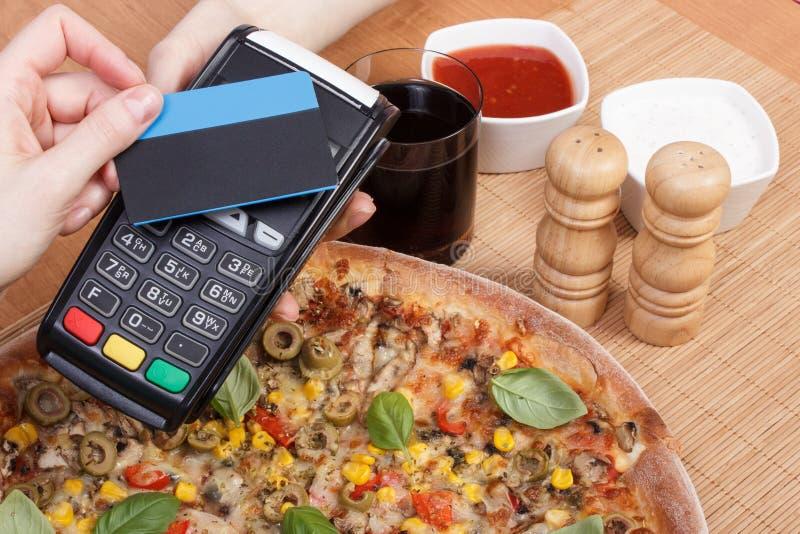 使用有不接触的信用卡的付款终端支付的在餐馆,财务概念,素食薄饼 库存图片
