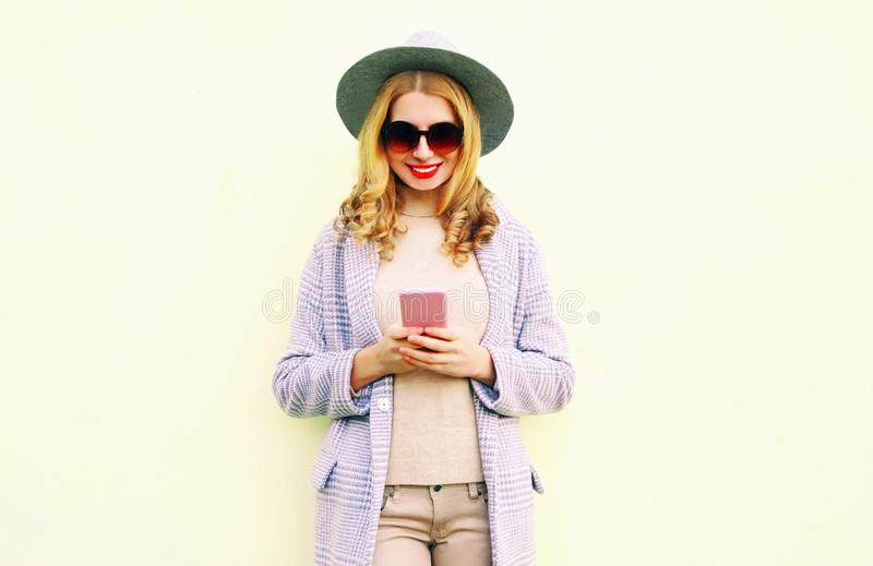 使用有卷发的年轻微笑的妇女电话在圆的帽子,在背景的外套夹克 免版税库存照片