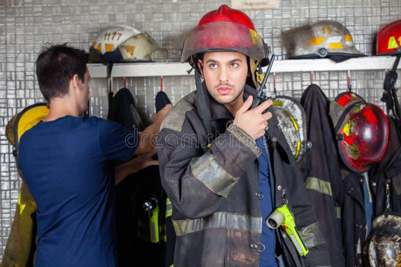 使用有同事的消防队员携带无线电话在背景 免版税图库摄影