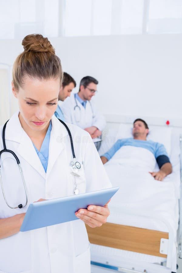 使用有后边同事和患者的医生数字式片剂 库存图片