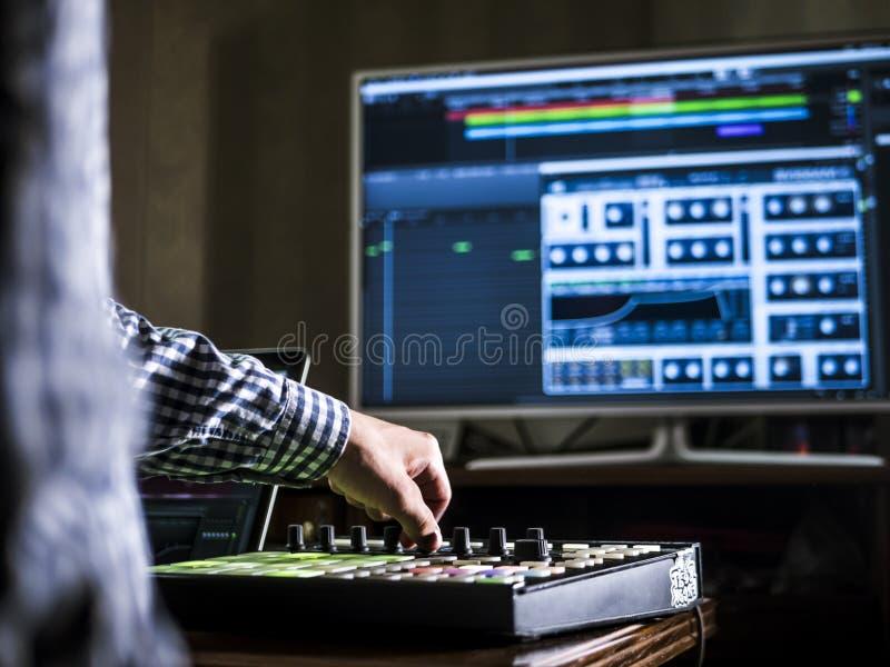 使用有大显示器的,新的现代设备关闭人` s手录音声音在录音音乐演播室 免版税库存照片