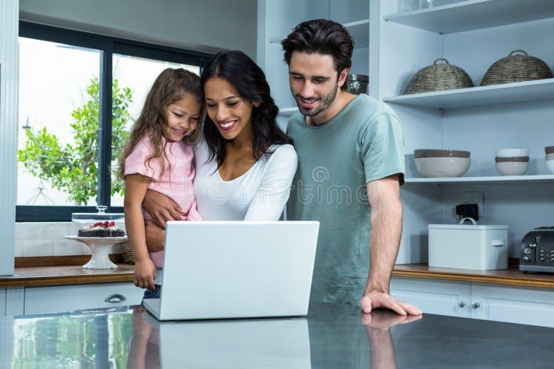 使用有女儿的微笑的父母膝上型计算机 图库摄影