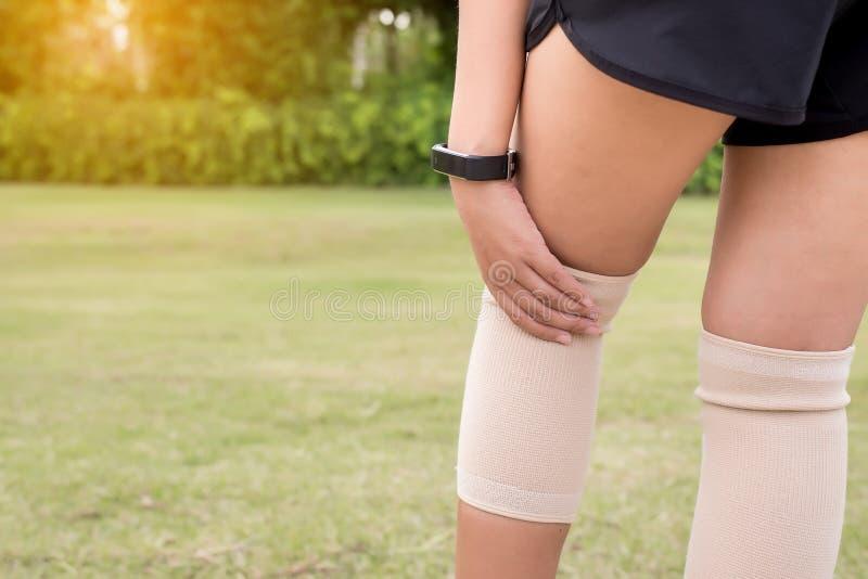 使用有她的腿的女性有弹性绷带,遭受在腿伤的痛苦的妇女在体育锻炼赛跑以后 库存照片