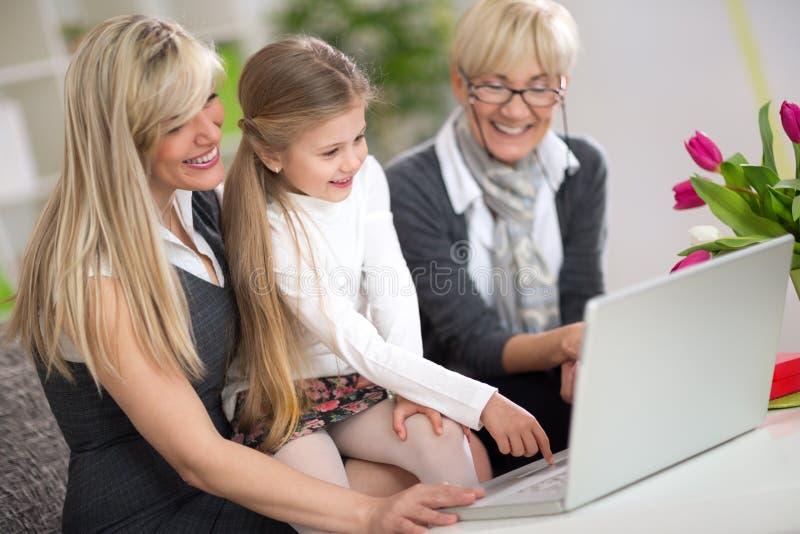使用有妈妈和祖母的逗人喜爱的女孩膝上型计算机 免版税库存图片
