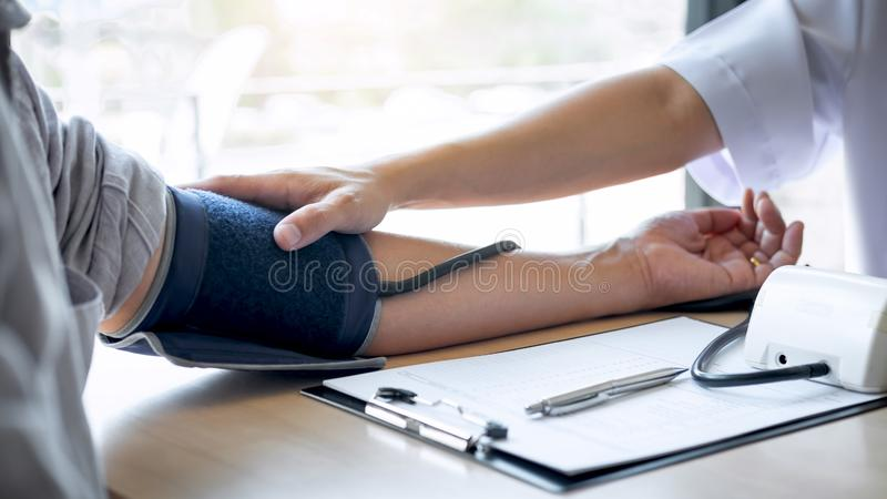 使用有审查的一名测量的血压检查病人医治,提出结果症状和推荐治疗方法 库存照片