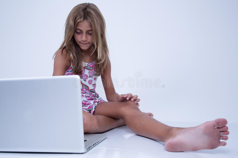 使用有担心的表示的女孩一台膝上型计算机 库存图片