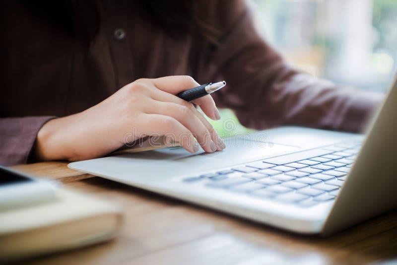 使用有智能手机的膝上型计算机和笔记本在手上的妇女选择的焦点 库存图片