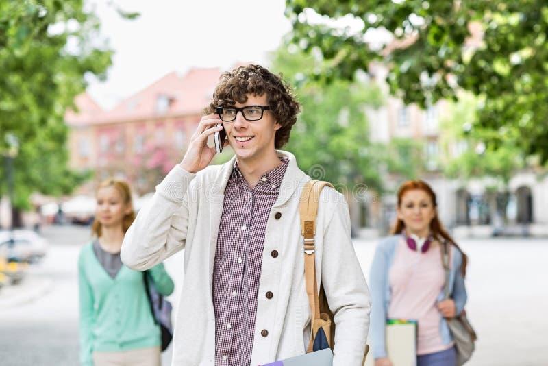 使用有朋友的微笑的年轻男学生手机在街道上的背景 免版税库存图片