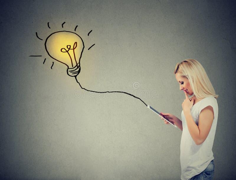 使用有电灯泡的体贴的妇女一台片剂计算机接通它 图库摄影