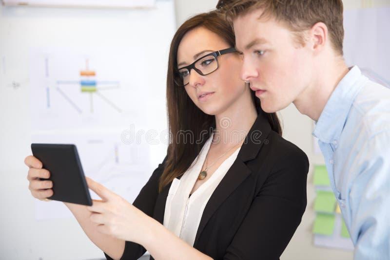 使用有男性同事的女实业家片剂计算机 库存照片