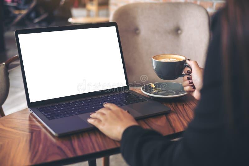 使用有空白的白色桌面屏幕的女实业家的大模型图象膝上型计算机,当喝在木桌上时的热的咖啡 图库摄影