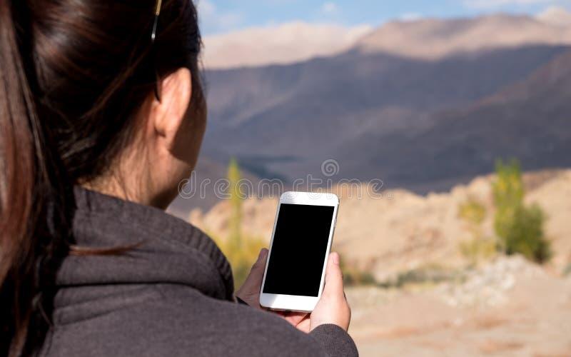 使用有空白的黑屏幕的妇女的大模型图象白色手机,当站立在山前面时 库存照片