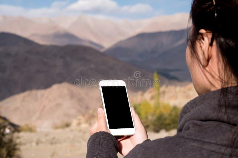 使用有空白的黑屏幕的妇女的大模型图象白色手机,当站立在山前面时 库存图片